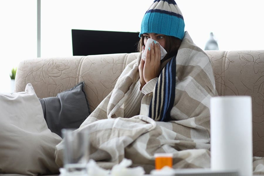 sick person sitting on couch with blankets and a hat on